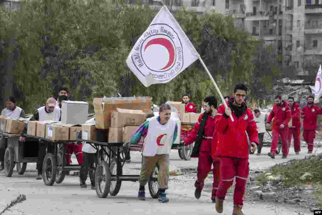 Members of the Syrian Red Crescent group escort Syrians and move aid supplies from a rebel-controlled area to a regime-held area of the northern Syrian city of Aleppo through the Garage al-Hajz crossing in the Bustan al-Qasr district.