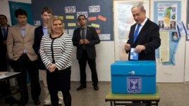 Israel's Prime Minister Benjamin Netanyahu (R) casts his ballot for the parliamentary election as his wife Sara (3rdL) stands nearby at a polling station in Jerusalem, January 22, 2013.