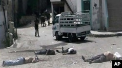 Dalam foto yang dirilis oleh oposisi Suriah, nampak para tentara Pemerintah Suriah - berdiri di dekat mayat-mayat yang bergelimpangan di desa Bayda, wilayah pegunungan di luar kota pantai Banias, Suriah (2/5).