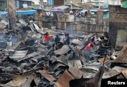 People inspect the damage as they stand amid the remains of properties that were burned by rioters in Kawangware slums in Nairobi, Kenya, Oct. 28, 2017.