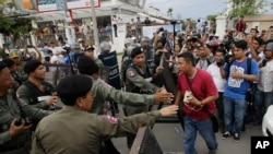 FILE PHOTO - Riot police officers stop journalists from entering a blocked main street near the Cambodia National Rescue Party (CNRP) headquarters, on the outskirts of Phnom Penh, Cambodia, Monday, May 30, 2016.