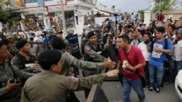 Riot police officers stop journalists from entering a blocked main street near the Cambodia National Rescue Party (CNRP) headquarters, on the outskirts of Phnom Penh, Cambodia, Monday, May 30, 2016. Police in Cambodia blocked an opposition protest march o