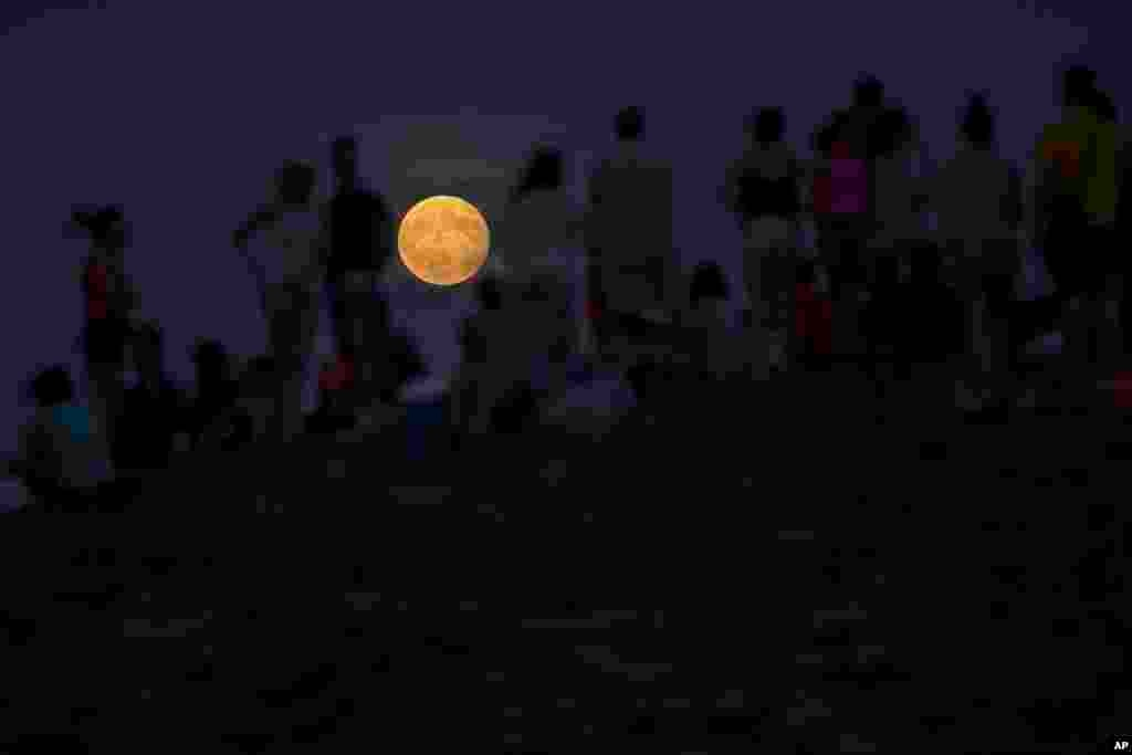 People watch at a rising full moon during a partial lunar eclipse atop a hill at the Tio Pio park in Madrid, Spain, Aug. 7, 2017.