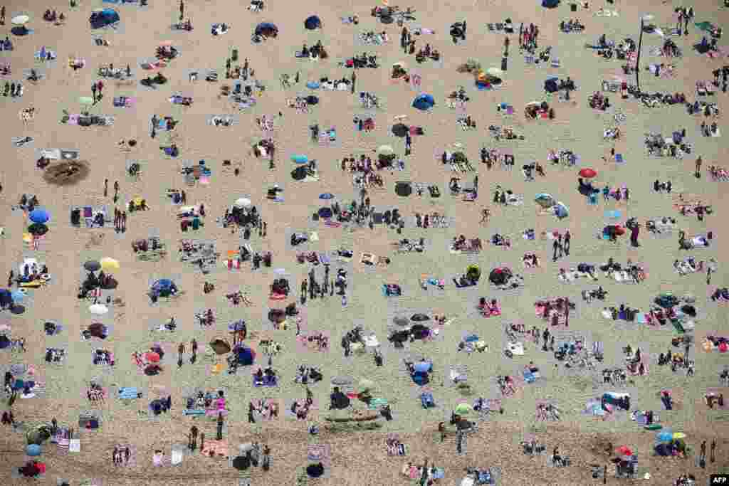 An aerial view of sunbathers crowding on the beach in Scheveningen, the Netherlands, during a warm summer day.