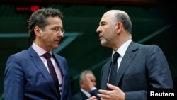 Eurogroup chairman Jeroen Dijsselbloem (L) talks to European Commissioner for economics, taxation and customs Pierre Moscovici (R) during an eurozone finance ministers meeting in Brussels, Jan. 26, 2015.