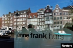 FILE - Reflections of tourists and canal houses are seen in the window of the Anne Frank museum in Amsterdam, April 24, 2013.