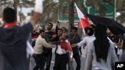 An unidentified Bahraini anti-government protester is carried to a vehicle to be taken to a hospital after being shot during a demonstration in Manama, February 18, 2011