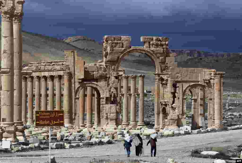 Syrian citizens walking in the ancient oasis city of Palmyra, 215 kilometres northeast of Damascus.
