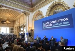 From left, Sarah Chayes from the Carnegie Endownment for International Peace,British Prime Minister Cameron, Afghan President Ghani and French magistrate Eva Jolly share a platform at the international anti-corruption summit, London, Britain, May 12, 2016.