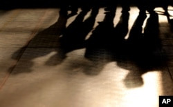 FILE - Shadows of laborers cast on the floor after an event for workers at a residential camp for laborers and managers, in Abu Dhabi, United Arab Emirates, April 6, 2016.
