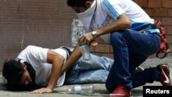 Un manifestante antigubernamental se recobra luego de ser atacado con gases lacrimógenos en San Cristóbal.