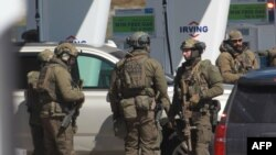 Members of the Royal Canadian Mounted Police (RCMP) tactical unit confer after the suspect in a deadly shooting rampage was neutralized at the Big Stop near Elmsdale, Nova Scotia, Canada, April 19, 2020.
