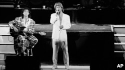 FILE - George Michael and Andrew Ridgeley of the British group WHAM! perform during a concert in Peking, China, April 7, 1985.