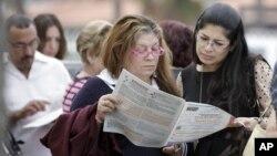 Para pemilih di Hialeah, Florida, membaca contoh kertas suara saat mengantre di TPS. (Foto: AP)