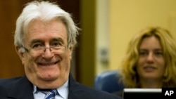 Suspected war criminal and former Bosnian Serb leader Radovan Karadzic smiles as he takes his seat on the defense bench in a courtroom to start his defense at the U.N. war crimes tribunal in The Hague, Netherlands, October 16, 2012.