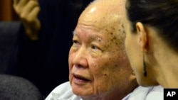 In this photo released by the Extraordinary Chambers in the Courts of Cambodia, Khieu Samphan, left, former Khmer Rouge head of state, sits in the court room during a hearing at the U.N.-backed war crimes tribunal, in Phnom Penh, Cambodia, Friday, Oct. 17, 2014. A U.N.-backed Cambodian tribunal has begun hearing the first genocide case against the country's brutal 1970s Khmer Rouge regime. (AP Photo/Extraordinary Chambers in the Courts of Cambodia, Nhet Sok Heng)