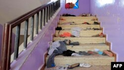 The belongings of Yemeni students are seen scattered on a staircase bearing blood stains at a school in the capital Sanaa on April 7, 2019, following explosions near the school.