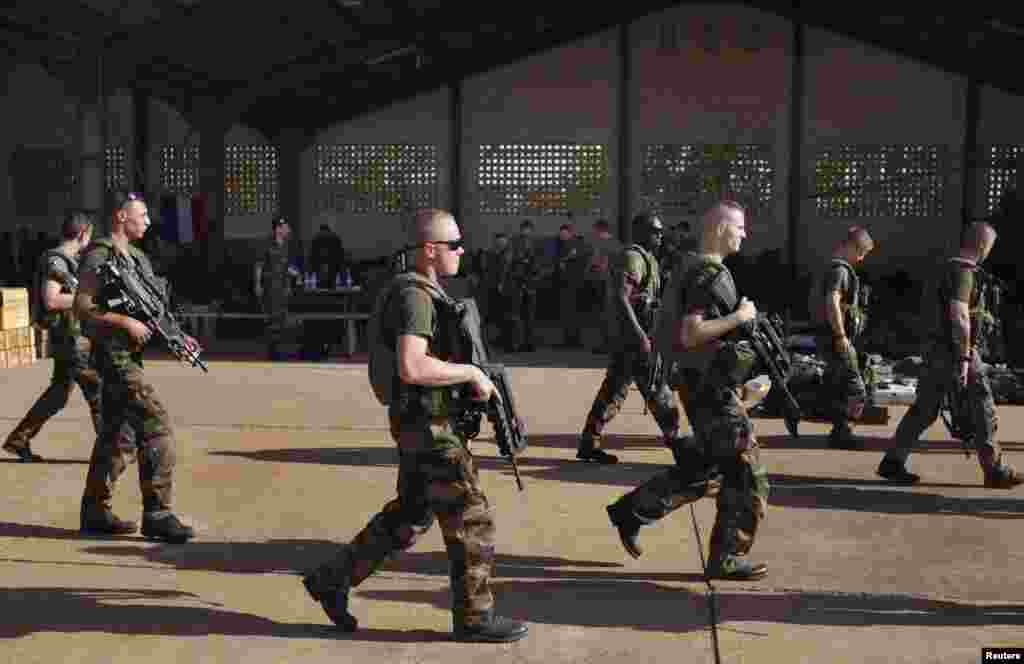 French soldiers walk past a hangar they are staying at the Malian army air base in Bamako, January 14, 2013.