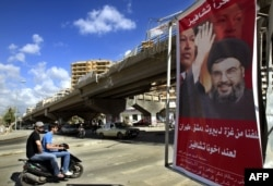 """FILE - A poster shows Hassan Nasrallah, the Secretary-General of Hezbollah, and Venezuela's President Hugo Chavez, along with a slogan that reads """"Gracias Chavez"""" is seen hanging from a destroyed bridge at the entrance of southern suburb of Beirut, Sept. 21, 2006."""