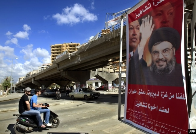 "FILE - A poster shows Hassan Nasrallah, the Secretary-General of Hezbollah, and Venezuela's President Hugo Chavez, along with a slogan that reads ""Gracias Chavez"" is seen hanging from a destroyed bridge at the entrance of southern suburb of Beirut, Sept. 21, 2006."