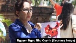 """Người biểu tình giơ cao hình ảnh về bản đồ tuyên bố chủ quyền gần như toàn bộ biển Đông của Trung Quốc, hay còn được gọi là """"đường lưỡi bò""""."""