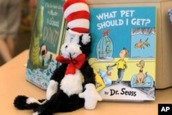 """FILE - A plush """"Cat in the Hat"""" toy is displayed next to """"What Pet Should I Get?,"""" the latest book by Dr. Seuss, on Tuesday, July 28, 2015 at a bookstore in Concord, N.H. (AP Photo/Holly Ramer)"""