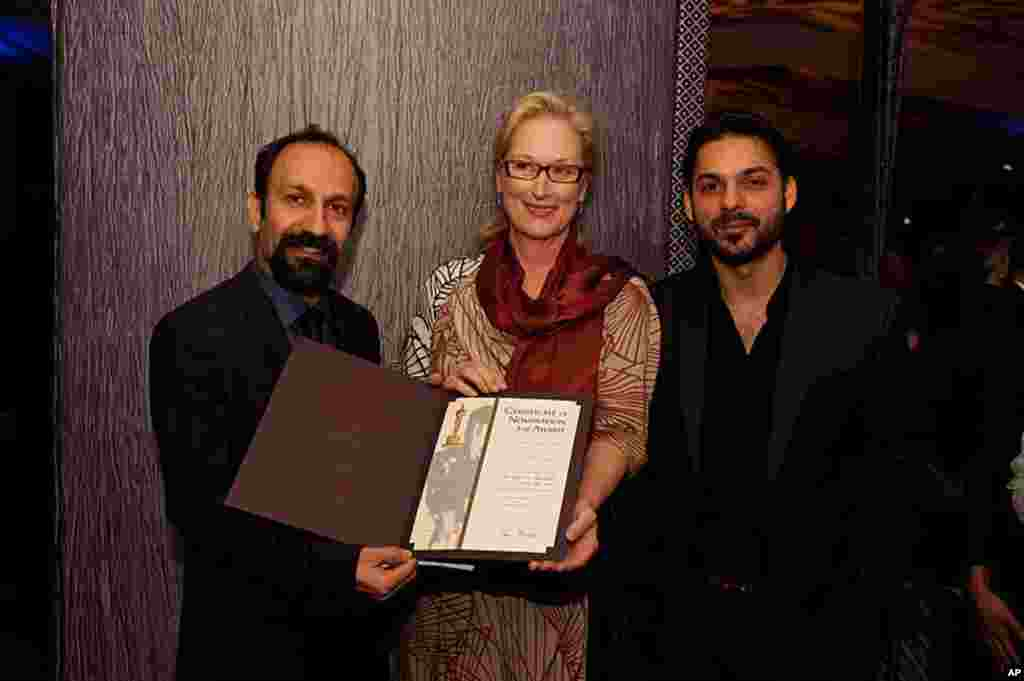 """.Asghar Farhadi, """" Separation"""" (left), accepts his certificate of nomination for the 84th Academy Awards from Meryl Streep (center) with actor Peyman Moadi (right)at a Foreign Language Film Award reception held in the Grand Lobby of the Samuel Goldwyn The"""