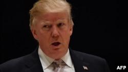 Le président Donald Trump parle aux journalistes à son club de golf à West Beach, le 14 janvier 2018.
