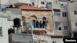 Penjaga Israel berdiri di balkon sebuah rumah yang dibeli warga Yahudi di daerah Arab di Silwan, Yerusalem timur (20/10).