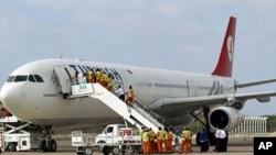 Employees work on a Turkish Airlines plane after its arrival at Aden Abdulle International Airport in Somalia's capital Mogadishu, March 6, 2012