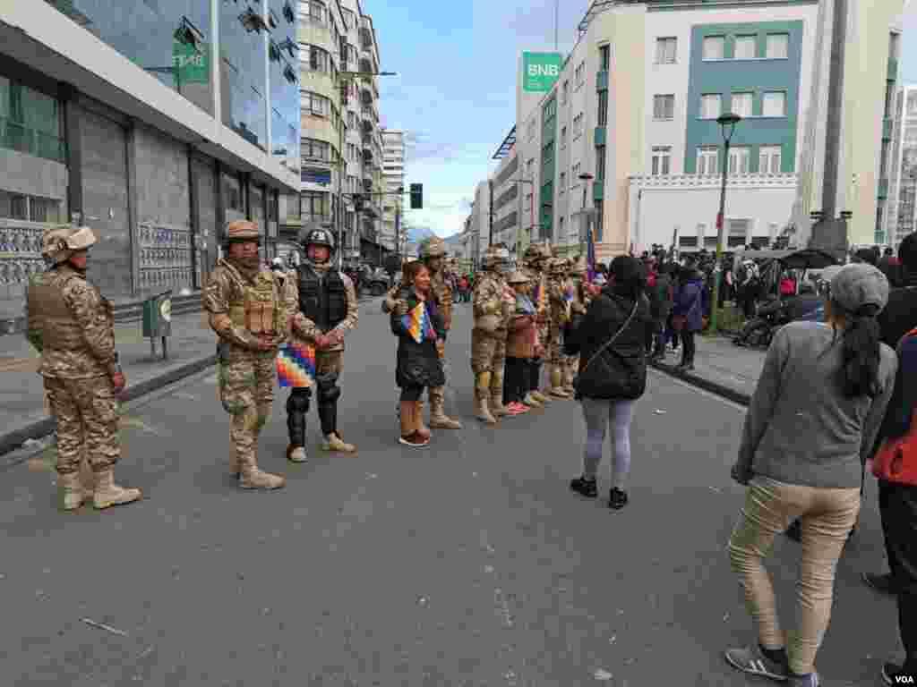 Personas que critican la unión entre militares y policías se sacan fotografías con los militares.