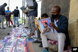 Ethiopians read newspapers and magazines reporting on the current military confrontation in the country, one of which shows a photograph of Prime Minister Abiy Ahmed, on a street in the capital Addis Ababa, Ethiopia, Nov. 7, 2020.