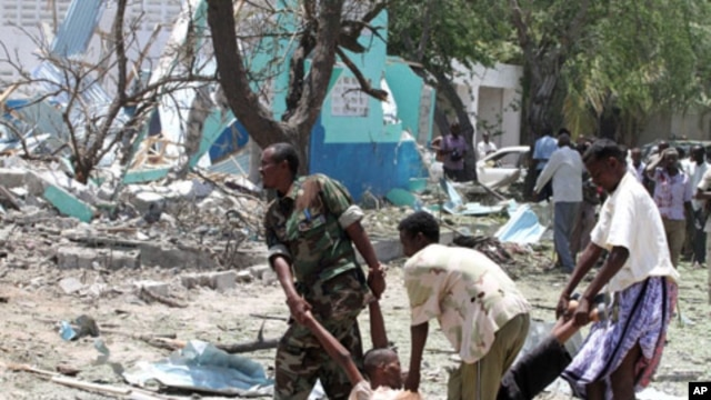 Somalia government soldiers carry a man killed during a suicide attack in Somalia's capital, Mogadishu, October 4, 2011.