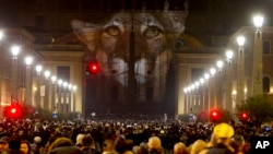 FILE - People gather to watch images projected on the facade of St. Peter's Basilica, at the Vatican, Dec. 8, 2015. Police say they have seized 3,500 fake Vatican parchments that were being sold to unsuspecting pilgrims taking part in Pope Francis' Holy Year celebrations.