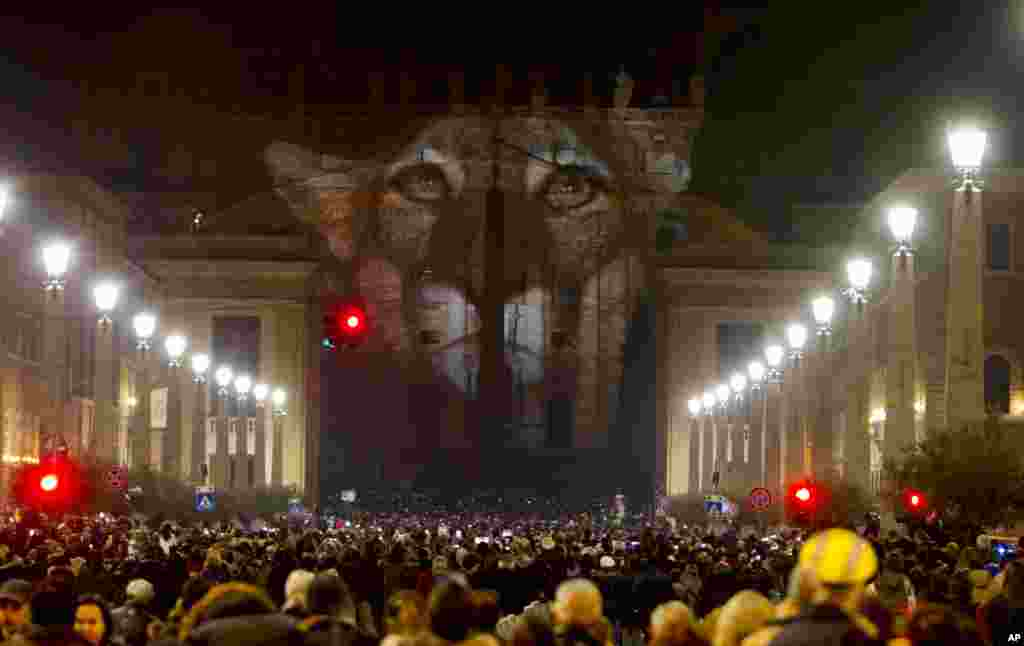People gather to watch images projected on the facade of St. Peter's Basilica, at the Vatican, Dec. 8, 2015.