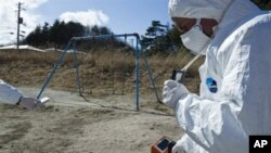 A handout picture released by Greenpeace and taken on March 27, 2011 shows Greenpeace members monitoring contamination levels at Iitate village, 40 km northwest of the crisis-stricken Fukushima nuclear plant, and 20 km beyond the official evacuation zone.