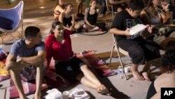 """Jóvenes """"dreamers"""" miran un documental sobre la migración mexicana en las afueras del Capitolio de Arizona, en junio."""