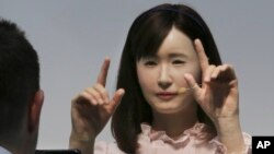 FILE - A prototype of Japanese electronics company Toshiba's female android Ms. Aiko Chihira performs sign language to a visitor during the annual CEATEC Japan advanced technologies show.