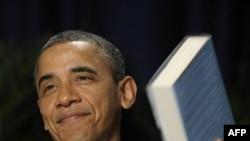 Predsednik Obama drži knjigu koju mu je poklonio autor i glavni govornik na ovogodišnjem molitvenom droučku, Erik Metaksas, 2. februara 2012.