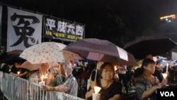 大批群眾冒雨留守在維園六四燭光晚會會場,堅持為六四死難者獻上燭光