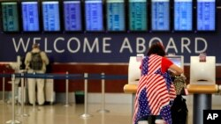 FILE - Judy Izzie, dressed in the theme of the American flag, checks in for her flight at Hartsfield-Jackson Atlanta International Airport.