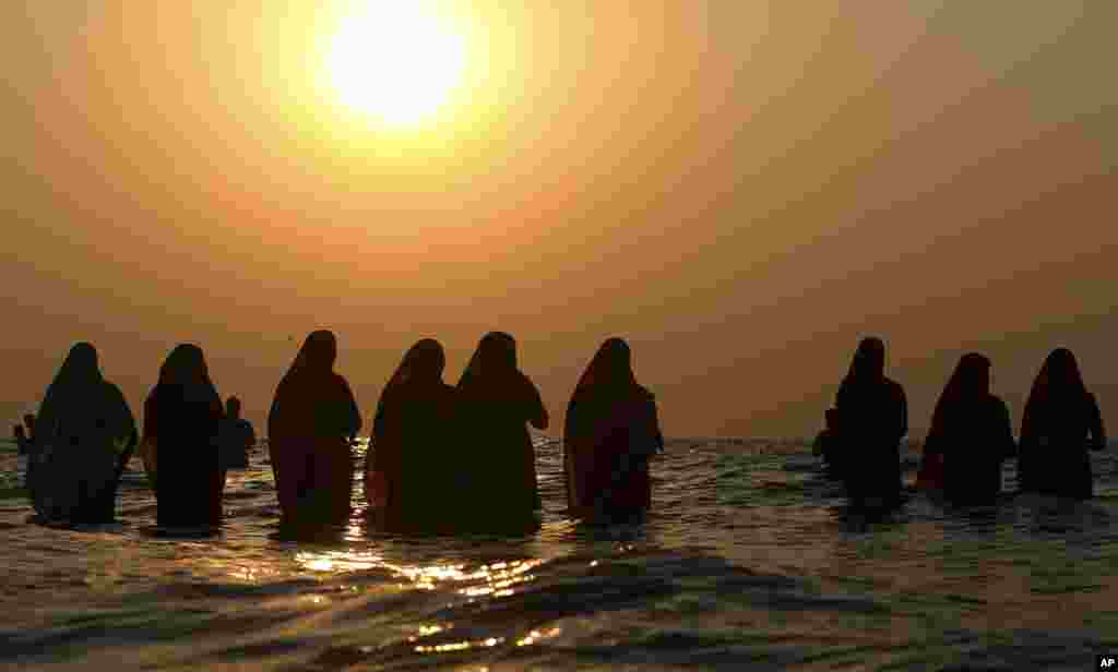 Hindu devotees offer prayers in the waters of the Arabian Sea at sunset during Chhath Puja festival in Mumbai, India.
