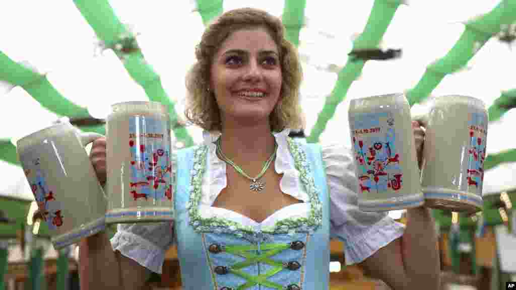 A woman named Elena takes a picture with the official Oktoberfest 2019 beer mugs in Munich, Germany.