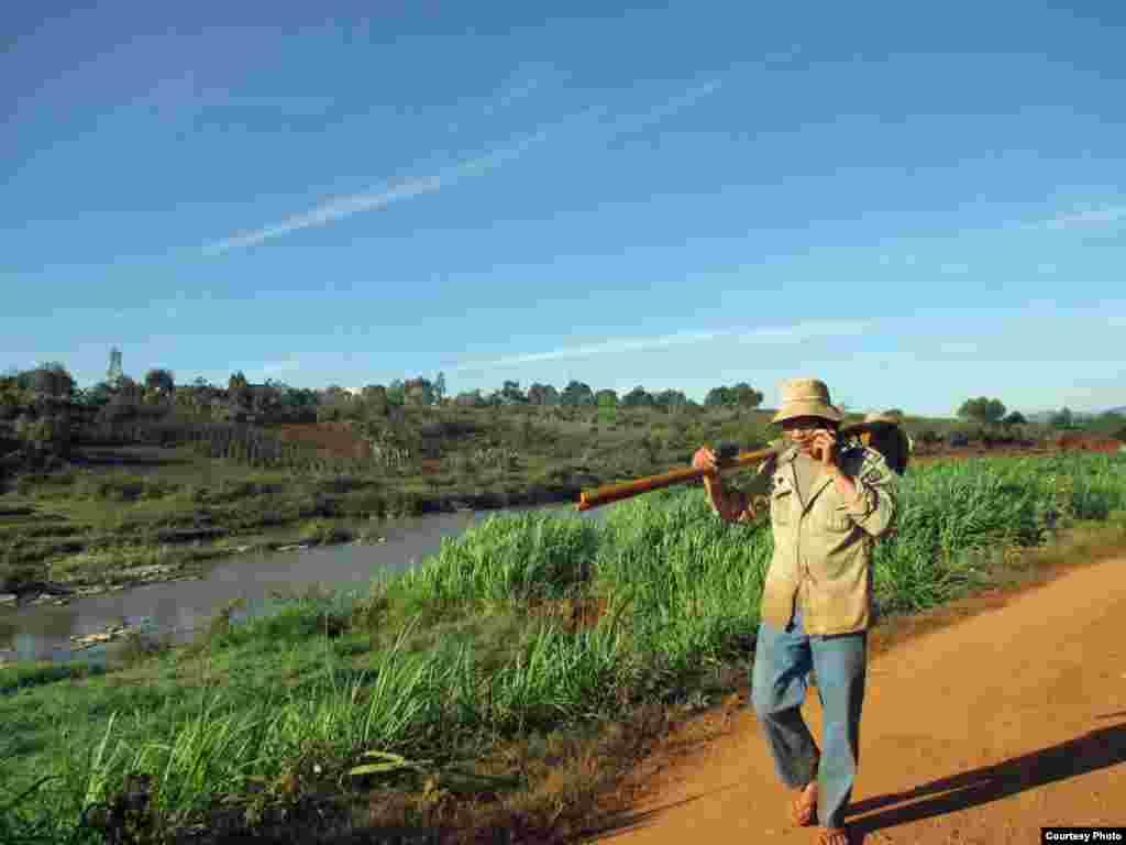 Một thanh niên ở Đà Lạt vác chiếc cuốc vừa đi vừa nói chuyện bằng điện thoại di động. (Ảnh của Hang Dinh Thi Thanh/Vietnam/độc giả VOA)