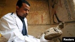 باستانشناس جسد مومیایی شده یک پرنده که در مقبره ای در استان سوهاج مصر پیدا شده را در دست گرفته است - ۵ آوریل ۲۰۱۹