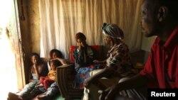 Rosina Mwitelela (nomor dua dari kanan) mengunjungi pasien HIV-AIDS (tengah) di rumahnya di Matero, Lusaka (17/4). Pakar kesehatan mendapat tantangan baru untuk mempersiapkan kehidupan bagi para penderita HIV-AIDS di masa depan.