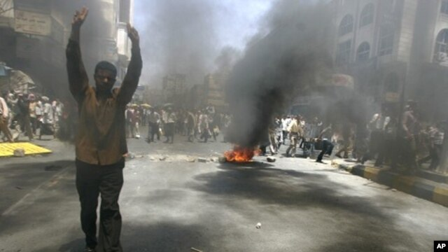 An anti-government protester flashes the victory sign during a demonstration to demand the ouster of Yemen's President Ali Abdullah Saleh in the southern city of Taiz May 12, 2011.