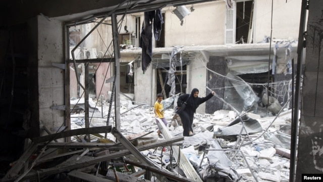 A woman walks through rubble from a building destroyed by shelling from forces loyal to Syrian President Bashar Al-Assad in downtown Aleppo August 1, 2012.