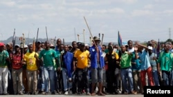 Mine workers protest outside the Lonmin mine in Rustenburg, northwest of Johannesburg, Jan. 23, 2014.