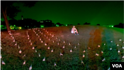 一名活動人士坐在華盛頓紀念碑附近擺放的國旗中,紀念在美國新冠肺炎大流行中喪生的180,000人。 (2020年08月27日)